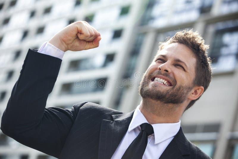 Ung lyckad affärsman som firar i stad arkivbild
