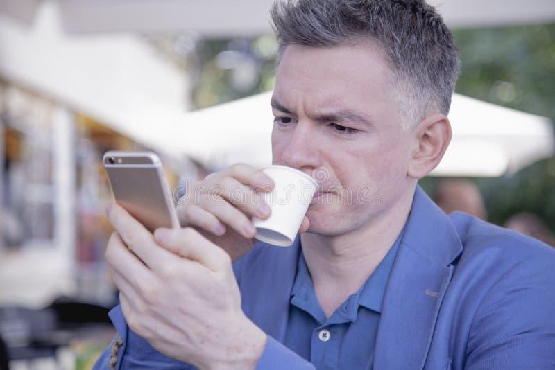 Ung lyckad affärsmaninnehavtelefon och drickakaffe royaltyfri foto