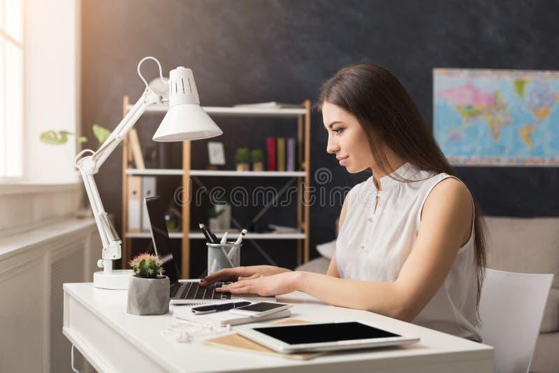 Ung lyckad resebyråman som arbetar på bärbara datorn arkivbild