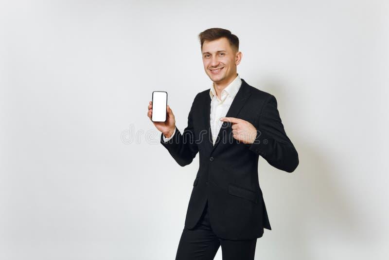 Ung lyckad stilig rik affärsman i svart dräkt på vit bakgrund för annonsering royaltyfria foton