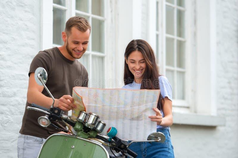 ung lycklig älska parinnehavöversikt utomhus nära sparkcykeln Se på översikt arkivbild