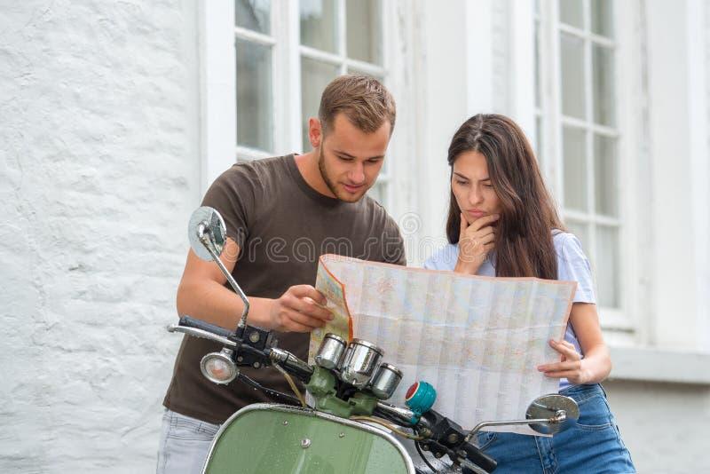 ung lycklig älska parinnehavöversikt utomhus nära sparkcykeln Se på översikt royaltyfria bilder