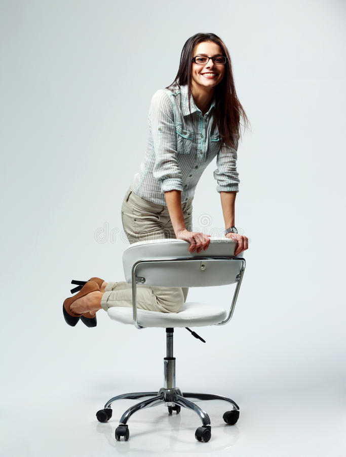 Ung lycklig affärskvinna som har gyckel på kontorsstol royaltyfria bilder