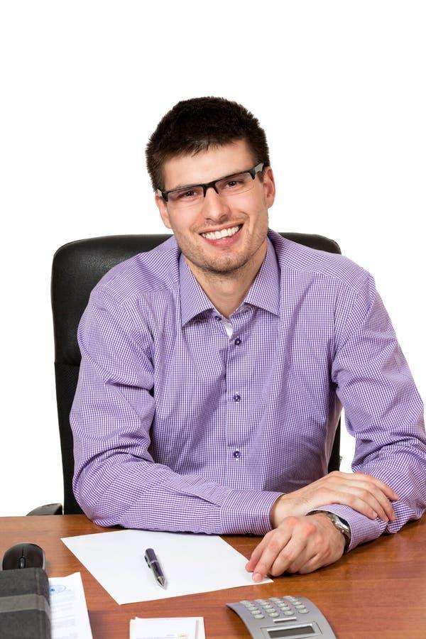 Ung lycklig affärsman som arbetar på hans skrivbord royaltyfri fotografi