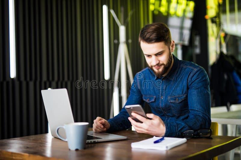 Ung lycklig affärsman som ler, medan läsa hans smartphone Stående av att le det läs- meddelandet för affärsman med smartphonen in royaltyfri bild
