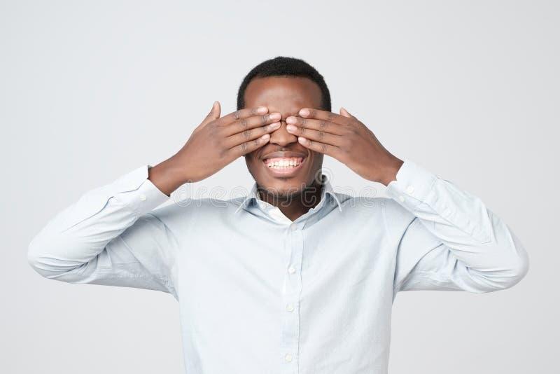Ung lycklig afrikansk man som täcker ögon med händer som väntar på födelsedaggåvan arkivbild
