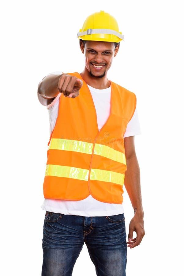 Ung lycklig afrikansk manbyggnadsarbetare som ler stundpointi arkivfoto