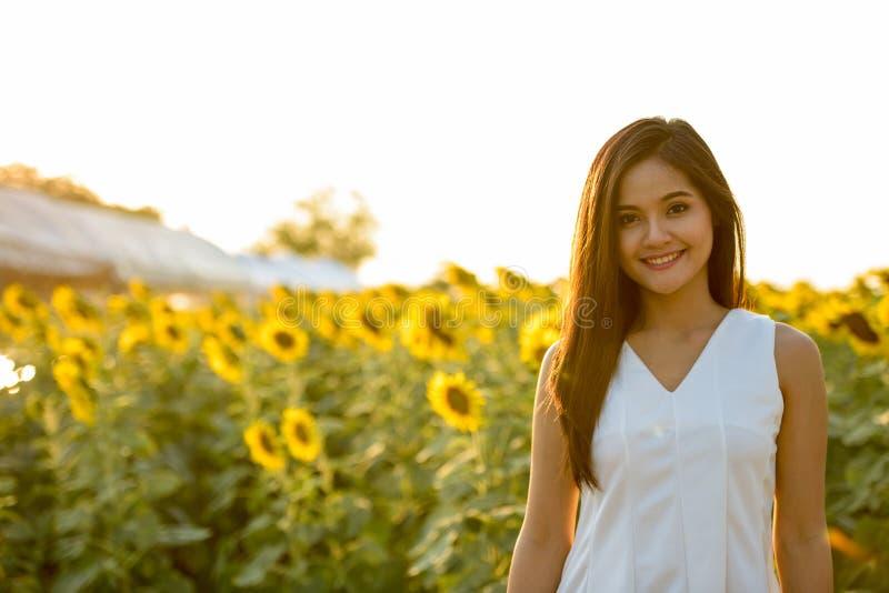 Ung lycklig asiatisk kvinna som ler i fältet av blommande sunflow arkivfoto