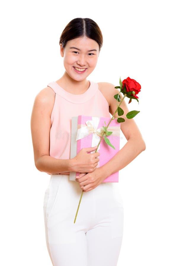 Ung lycklig asiatisk kvinna som ler, medan rymma den röda rosen och gåvan royaltyfri foto