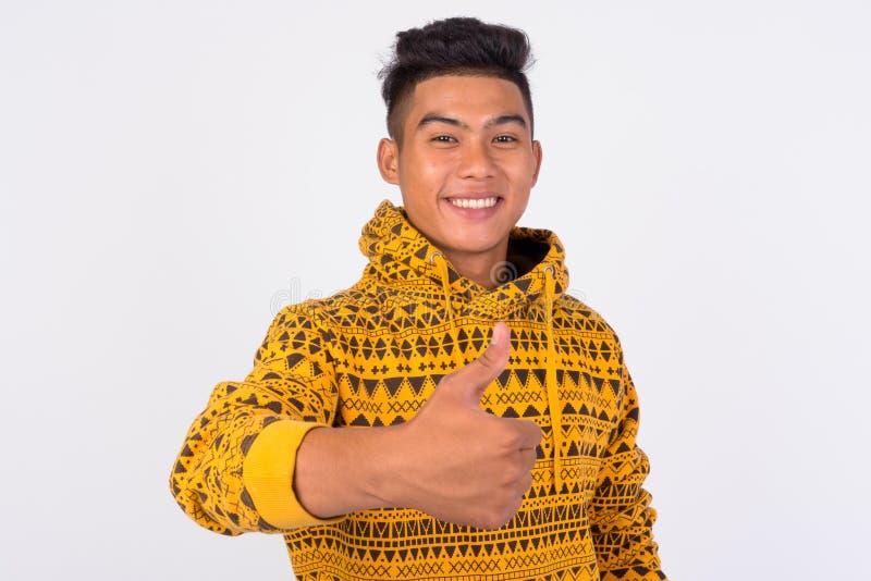 Ung lycklig asiatisk man med hoodien som ger upp tummar arkivbild