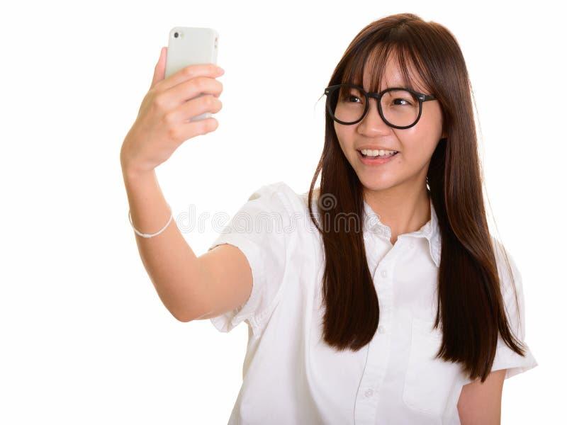 Ung lycklig asiatisk tonårs- flicka som ler, medan ta selfie med royaltyfri fotografi