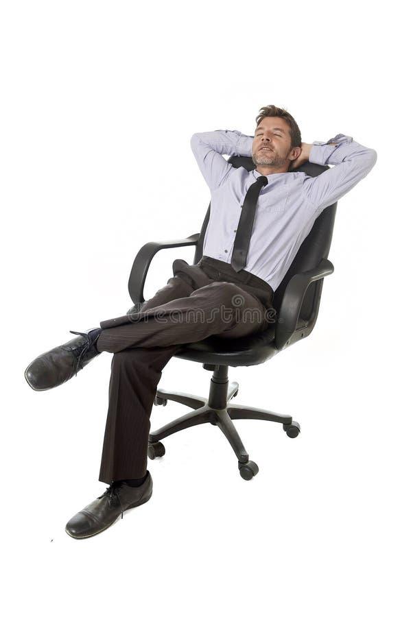 Ung lycklig attraktiv kopplat av sammanträde för affärsman benägenhet på kontorsstol som isoleras på vit royaltyfri foto