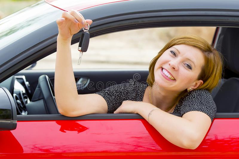 Ung lycklig attraktiv kvinna som ler stolt sammanträde på tangenten för innehav för chaufförplats och visningbili ny bilköp och h royaltyfri fotografi