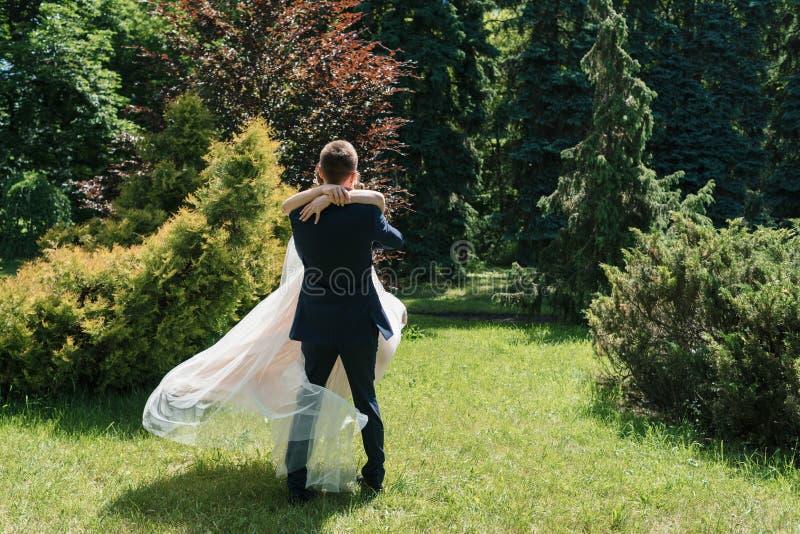 Ung lycklig brölloppardans och hagyckel i solig gifta sig dag Brudgum Spinning Bride kl?nningen framkallar i vinden royaltyfria foton