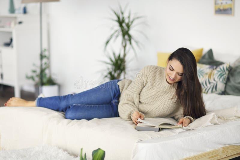 Ung lycklig brunettkvinna med den bärande tröjan för bok royaltyfri fotografi