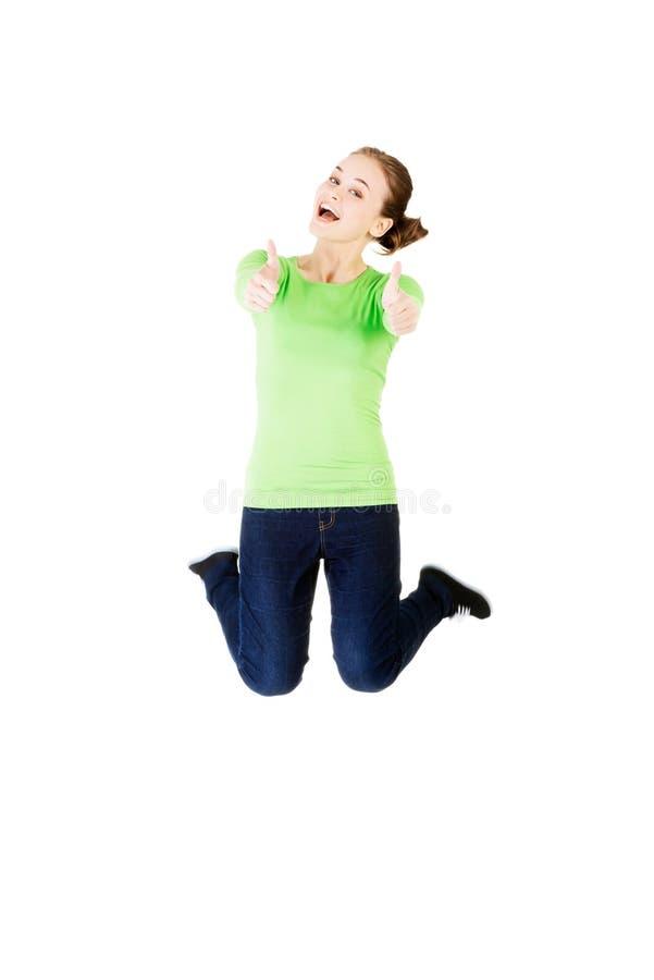 Ung lycklig caucasian kvinnabanhoppning i luften med tummar upp royaltyfri foto