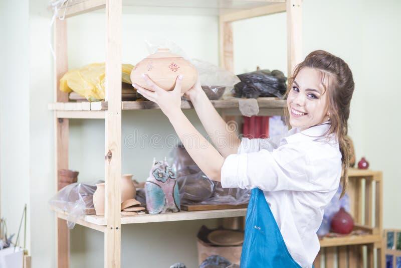 Ung lycklig Caucasian kvinnlig keramiker som rymmer den stora Argilbunken i seminarium royaltyfria bilder