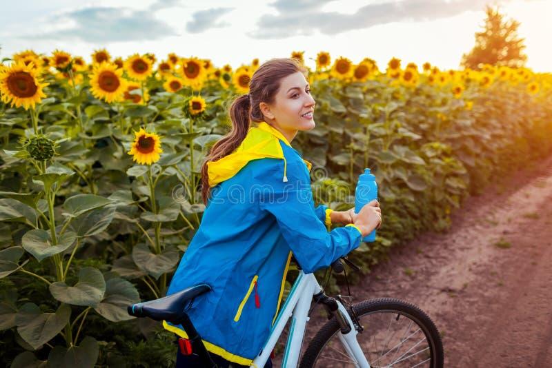 Ung lycklig cykel för kvinnacyklistridning i solrosfält Sommarsportaktivitet Sund livsstil royaltyfria foton