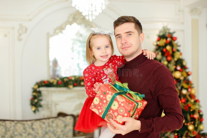 Ung lycklig fader som håller den lilla dottern med gåva, julgran i bakgrund arkivfoto