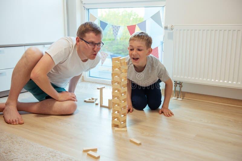 Ung lycklig fader som spelar med hans son med träkvarter på golvet arkivbild