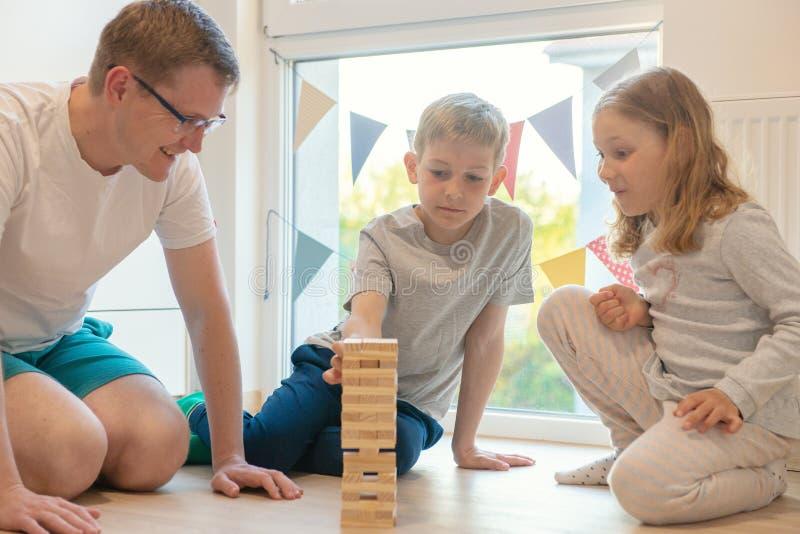 Ung lycklig fader som spelar med hans två gulliga barn med träkvarter royaltyfria foton