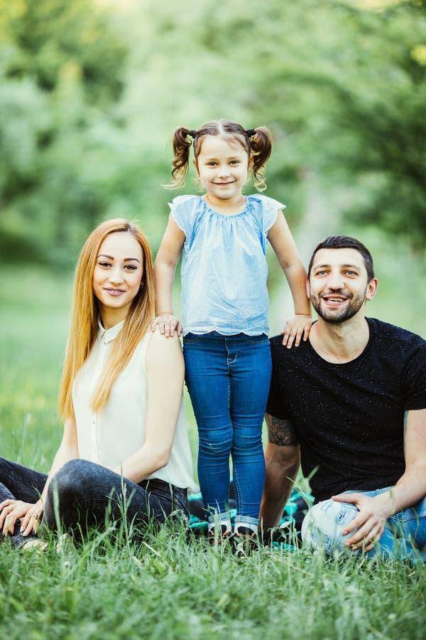 Ung lycklig familj av tre som har utomhus- gyckel tillsammans Lycka och harmoni i familjeliv Familjgyckel utanför royaltyfri fotografi