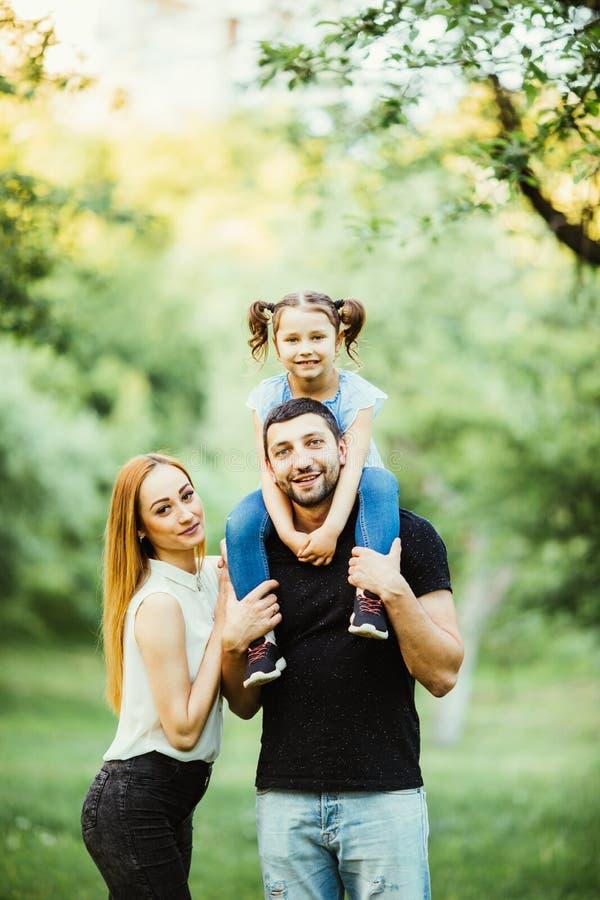 Ung lycklig familj av tre som har utomhus- gyckel tillsammans Nätt lite dotter på henne faderbaksida  fotografering för bildbyråer