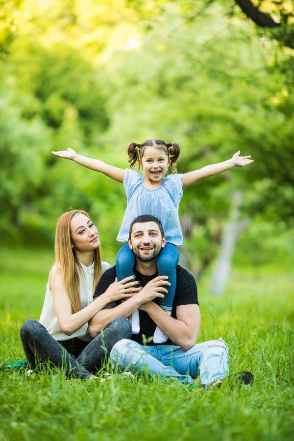 Ung lycklig familj av tre som har utomhus- gyckel tillsammans Nätt liten dotter på hennes fader tillbaka med lyckliga lyftta händ royaltyfria bilder