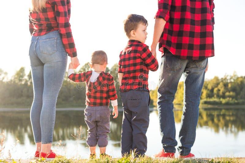 Ung lycklig familj med barn som har gyckel i natur F?r?ldrar g?r med barn i parkerar royaltyfri bild