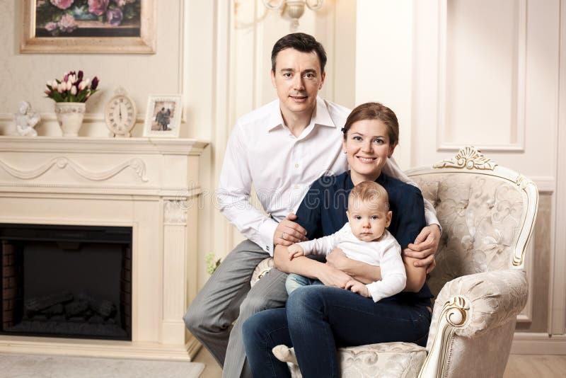 Ung lycklig familj med en behandla som ett barn inomhus royaltyfri fotografi