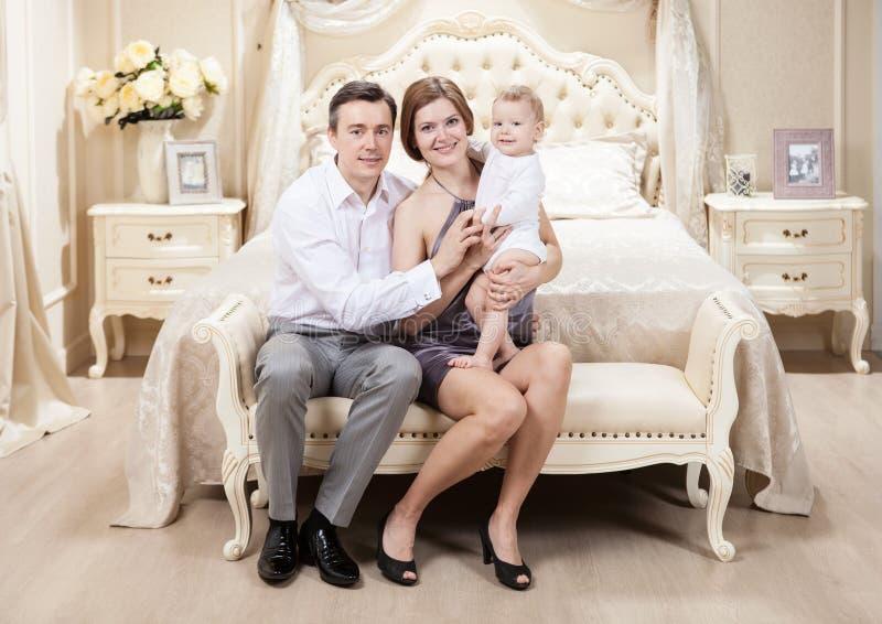 Ung lycklig familj med en behandla som ett barn på säng arkivfoto