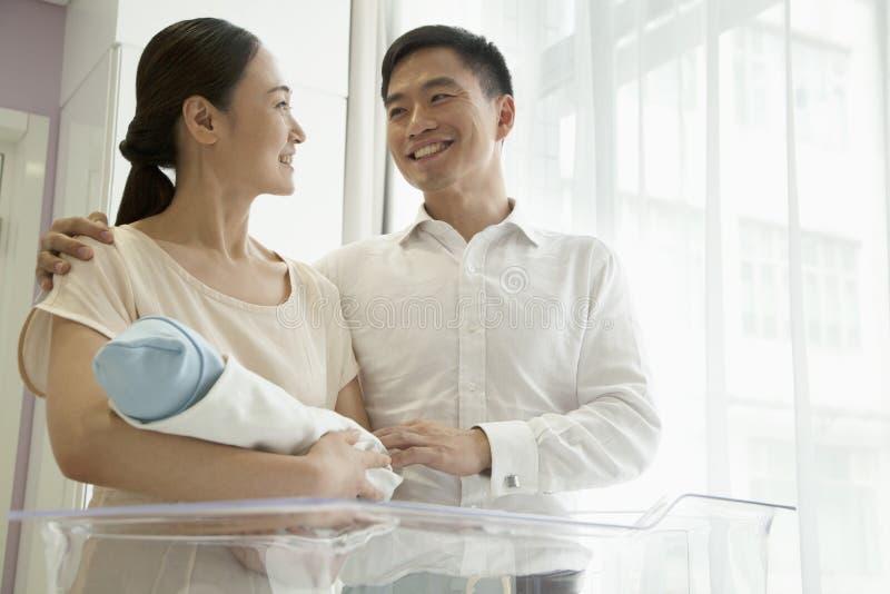 Ung lycklig familj som rymmer deras nyfött i sjukhusbarnkammaren royaltyfri bild