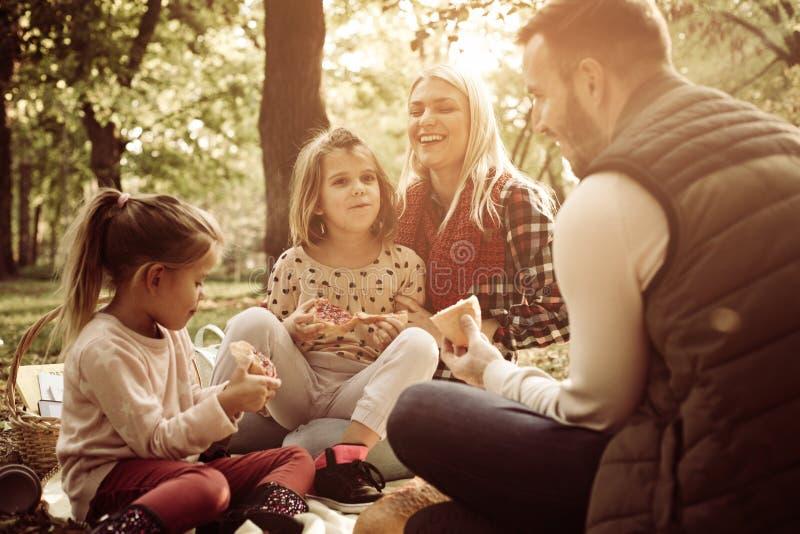 Ung lycklig familj som tillsammans tycker om i picknick i skog arkivfoton