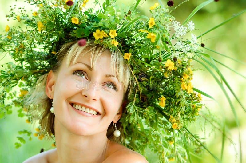 Ung lycklig flicka i krans av gräs och blommor Sommardag i en äng arkivbild