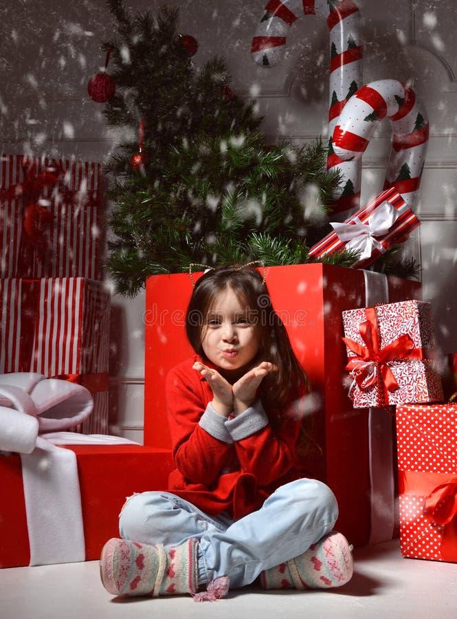 Ung lycklig flicka in med den stora närvarande gåvan som ler nära enormt rött royaltyfri fotografi