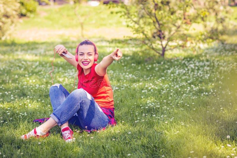 Ung lycklig flicka med hörlurar och smartphonen som lyssnar till musien arkivfoto