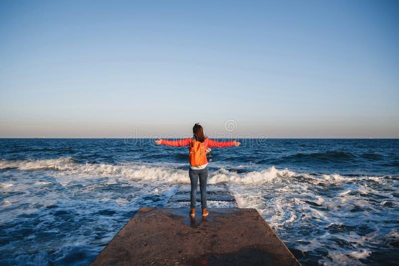 Ung lycklig flicka med orange ryggsäckanseende på en sjösida som andas ny luft som lyfter armar som tycker om sikten arkivbilder