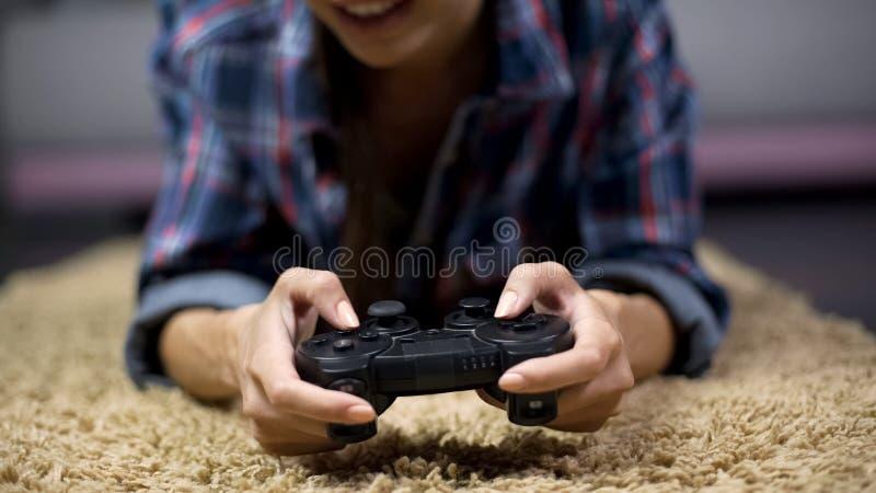Ung lycklig flicka som spelar videospel på konsolen som segrar mot grabbvänner royaltyfri bild