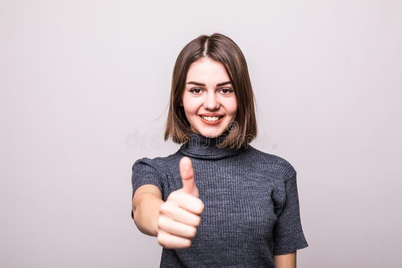 Ung lycklig gladlynt kvinnavisningtumme upp på grå färger royaltyfri fotografi