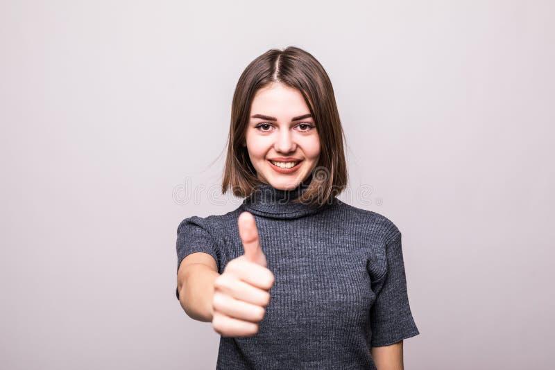 Ung lycklig gladlynt kvinnavisningtumme upp på grå färger arkivfoto