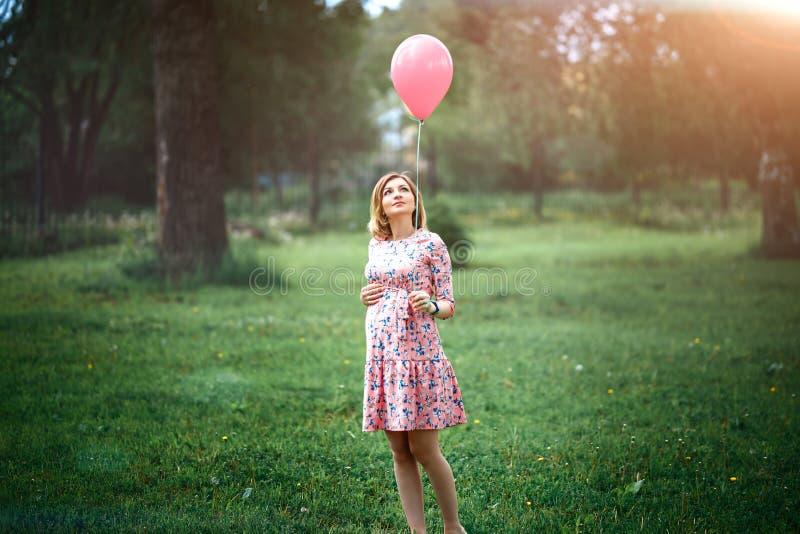 Ung lycklig gravid kvinna med den rosa ballongen utomhus royaltyfri fotografi
