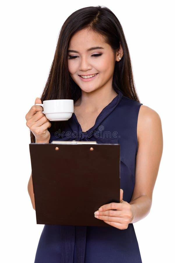 Ung lycklig h?rlig asiatisk drinki f?r stund f?r kvinnainnehavskrivplatta arkivfoto
