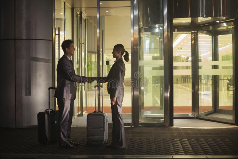 Ung lycklig handshaking för affärsfolk förutom kontoret på natten arkivbilder