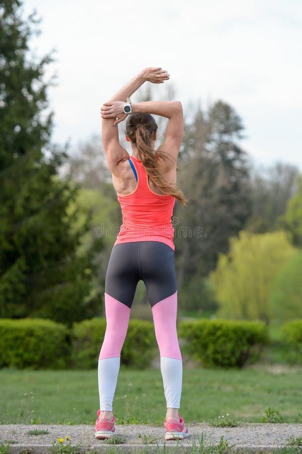 Ung lycklig idrottsman nen att göra sträckning av övningar utomhus på PA arkivfoton