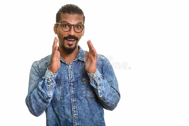 Ung lycklig indisk man som ser den förvånade studioståenden mot vit bakgrund arkivfoton