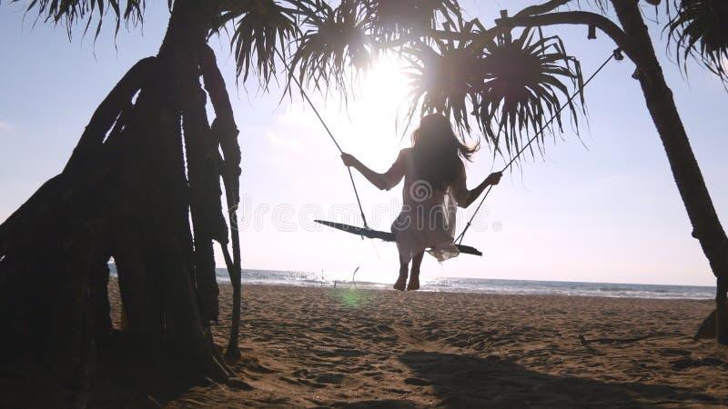 Ung lycklig kvinna i baddräkt och skjorta som kopplar av på gunga på den tropiska havstranden Härligt flickasammanträde på gunga  royaltyfria bilder