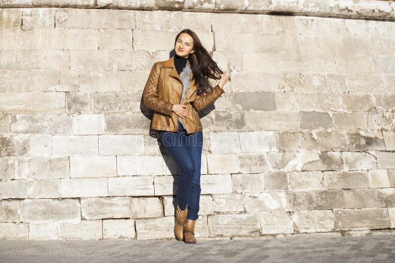 Ung lycklig kvinna i brunt läderomslag royaltyfria bilder