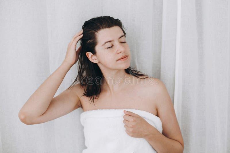 Ung lycklig kvinna i den vita handduken som applicerar hårbalsammaskeringen på hår i badrum Hår- och kroppomsorg Slank sexig kvin arkivbilder