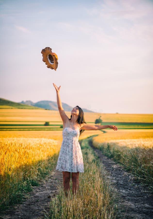 Ung lycklig kvinna i ett vetefält med den vita klänningen royaltyfri foto