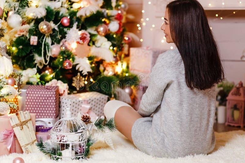 Ung lycklig kvinna i stucken tröja delikat juldekor, rosa garneringar på julgranen Kvinnasammanträde arkivfoto